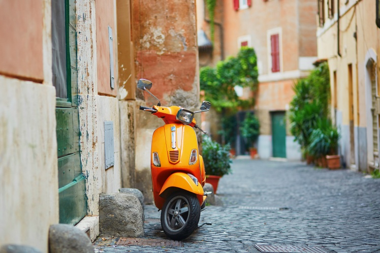 Old fashioned orange motorbike on a street of Trastevere district, Rome